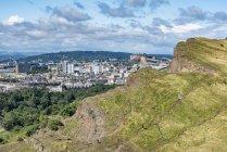 Regno Unito, Scozia, Edimburgo, scogliera di Salisbury Crags e la città vecchia con il Castello di Edimburgo — Foto stock