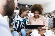 Due giovani donne sorridenti che guardano documenti in un caffè — Foto stock