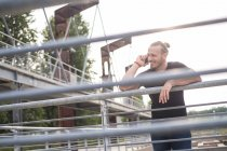 Усміхнений чоловік на телефоні, спершись на перила — стокове фото
