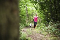 Young woman jogging with dog in forest — Stock Photo