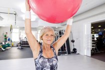 Reife Frau hebt Fitnessball hoch — Stockfoto
