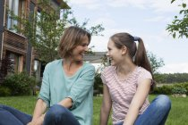 Happy mother and daughter sitting in garden — Stock Photo