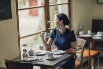 Young woman in a cafe looking out of window — Stock Photo