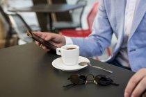 Homme d'affaires en tenant le téléphone cellulaire de café — Photo de stock