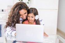 Glückliches junges Mädchen und ihre kleine Schwester mit Laptop und Kopfhörer — Stockfoto
