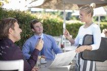 Kellnerin im Gespräch mit zwei Geschäftsleute im externen restaurant — Stockfoto