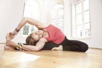 Женщина растягивается в Parivrtta Uphavistha Конасана йога поза в студии — стоковое фото