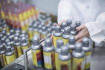 Operaio con bottiglie dello spruzzo in fabbrica medica — Foto stock
