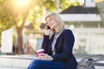 Улыбаясь блондинка предприниматель на телефоне — стоковое фото
