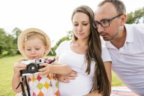Happy family in park, daughter playing with camera — Stock Photo