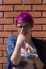 Portrait de jeune femme riante aux cheveux teints ajustant ses lunettes — Photo de stock