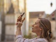 Francia, Chartres, giovane donna che scatta foto con smartphone davanti a Notre-Dame de Chartres — Foto stock