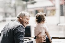 Businessman with little daughter working on laptop in cafe — Stock Photo