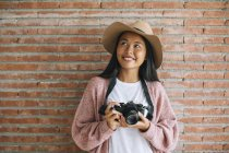 Giovane donna in piedi con macchina fotografica — Foto stock