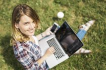 Smiling young woman sitting on a meadow using laptop and smartphone — Stock Photo