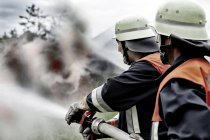 Fire brigade extinguishing fire in nature — Stock Photo