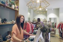 Shop assistant at counter in a boutique — Stock Photo