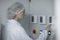 Femme en vêtements de travail protecteurs d'utiliser la machine — Photo de stock
