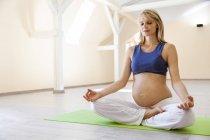 Пренатальная йога, женщина медитирует, лотос асана — стоковое фото