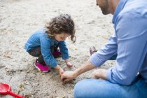 Father playing with daughter in sandbox — Stock Photo