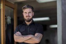 Portrait of handsome bearded barber at barbershop — Stock Photo