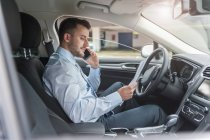 Businessman on cell phone in car — Stock Photo