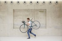 Man carrying bicycle on shoulder — Stock Photo