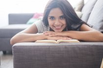 Portrait of smiling teenage girl lying on the couch with a book — Stock Photo
