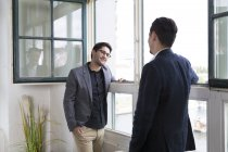 Two businessman standing at the window, talking — Stock Photo