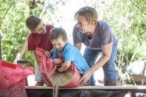 Father and sons filling sand into sandpit — Stock Photo