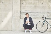 Businessman with bicycle using cell phone — Stock Photo