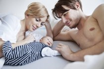 Parents looking at newborn baby in bed — Stock Photo