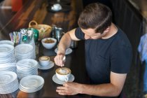 Barista preparing cappuccino in a cafe — Stock Photo
