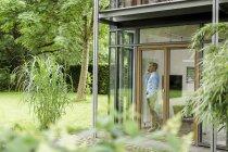 Mann telefoniert in seinem Haus und schaut durch Fenster — Stockfoto