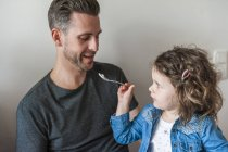 Daughter feeding her father — Stock Photo