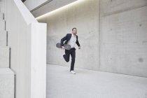 Businessman running with skateboard — Stock Photo