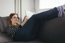 Jeune femme reposante sur le canapé avec sa tablette — Photo de stock