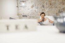 Жінка сидить на дивані і проведення чашку чаю — стокове фото