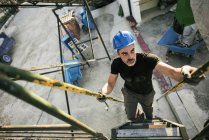 Worker wearing helmet climbing upstairs — Stock Photo
