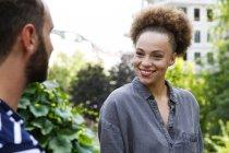 Giovane donna sorridente all'uomo nel parco — Foto stock