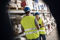 Man and woman taking stock in warehouse — Stock Photo
