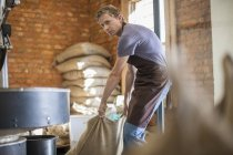Coffee roaster with bag of beans — Stock Photo