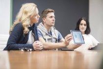 Jóvenes empresarios que muestran información sobre tabletas digitales en reuniones de negocios - foto de stock