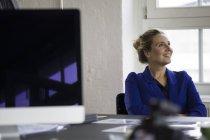 Підприємець, сидячи в офісі з обіймами перетнула, посміхаючись — стокове фото