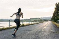 Vista posteriore della giovane donna che corre all'aperto — Foto stock