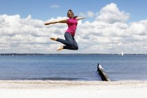 Happy young woman jumping in the air on the beach — Stock Photo