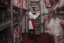 Жінка з буфера обміну в бійня холодильній камері — стокове фото