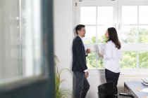 Businessman and woman standing at office window, disussing — Stock Photo