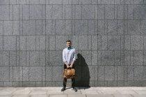 Homme d'affaires, debout devant un gris — Photo de stock