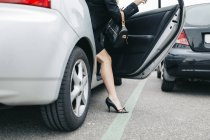 Woman wearing high heels getting out of car — Stock Photo
